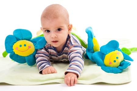 Studio portrait of a newborn caucasian boy with toy flowers photo