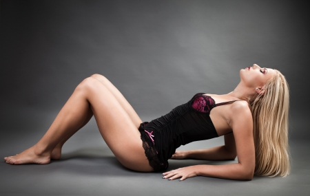 Full length portrait of a beautiful woman wearing lingerie while laying on the floor Stock Photo - 16324197