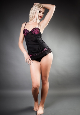 Full length portrait of a beautiful woman wearing lingerie while standing with hand on hip photo