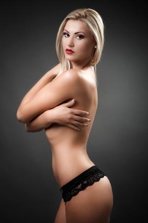 그녀의 팔을 그녀의 가슴을 커버하는 아름다운 토플리스 여자의 초상화