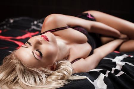 mujer rubia desnuda: Retrato de una mujer hermosa que desgasta la ropa interior al tiempo que sienta en la cama Foto de archivo