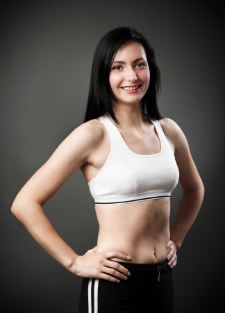 Studio portrait of a beautiful sporty woman standing with hands on hips Stock Photo - 16324196