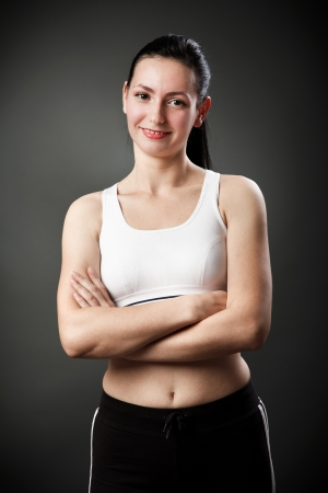 Studio portrait of a beautiful sporty woman with crossed arms photo