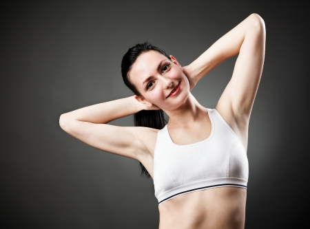 Studio portrait of a beautiful sporty woman stretching her body Stock Photo - 16324177