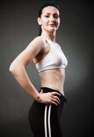 Studio portrait of a beautiful sporty woman standing with hands on hips photo