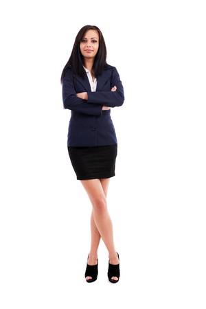 legs folded: Full length portrait of a beautiful latin businesswoman standing with crossed arms and legs isolated on white background Stock Photo
