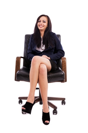 Full length portrait of a beautiful hispanic businesswoman sitting on an armchair isolated on white background photo