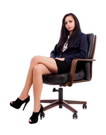 legs crossed: Full length portrait of a beautiful hispanic businesswoman sitting on an armchair isolated on white background Stock Photo