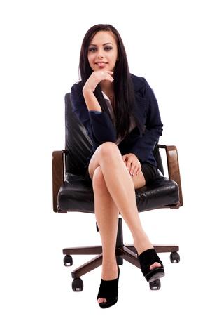 mani incrociate: Ritratto di lunghezza completa di un pensiero bella imprenditrice ispanico, mentre seduto su una poltrona isolato su sfondo bianco Archivio Fotografico