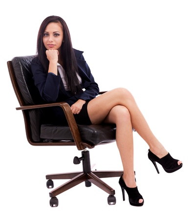 crossed legs: Full length portrait of a beautiful hispanic businesswoman thinking while sitting on an armchair isolated on white background