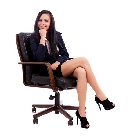 Full length portrait of a beautiful hispanic businesswoman thinking while sitting on an armchair isolated on white background photo