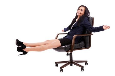 satisfied people: Full length portrait of a beautiful hispanic businesswoman sitting on an armchair isolated on white background Stock Photo