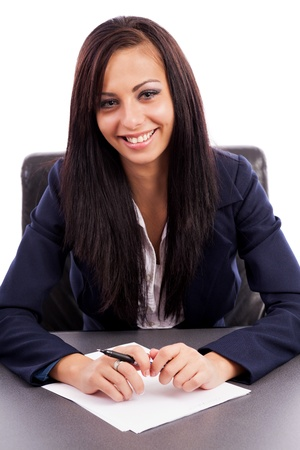 Portrait of a hispanic businesswoman writing while sitting at desk Stock Photo - 16324241