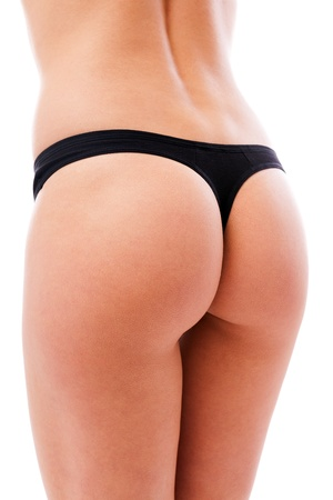 Closeup of a sexy womans ass wearing black lingerie isolated on white background
