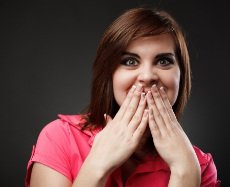 withhold: Surprised and amused young woman bursting in laugh