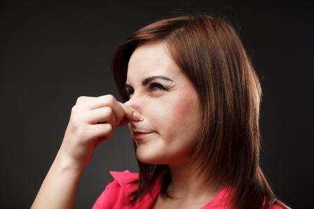 Closeup portrait d'une jeune femme tenant son nez à cause d'une mauvaise odeur