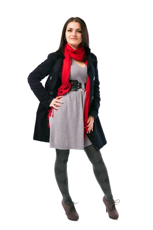 Full length portrait of a young woman standing with hand on hip wearing coat isolated on white background photo