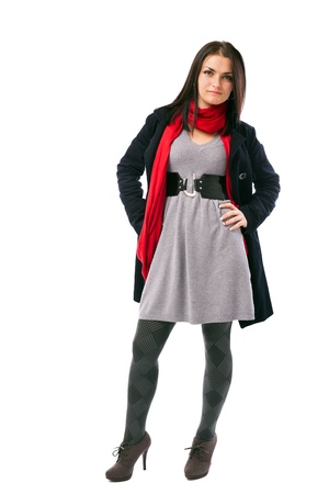 Full length portrait of a young woman standing with hands on hips wearing coat isolated on white background photo