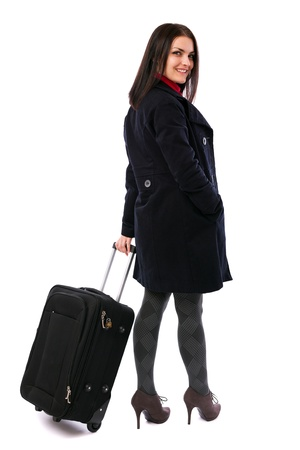 Full length portrait of a young woman holding a luggage isolated on white background photo