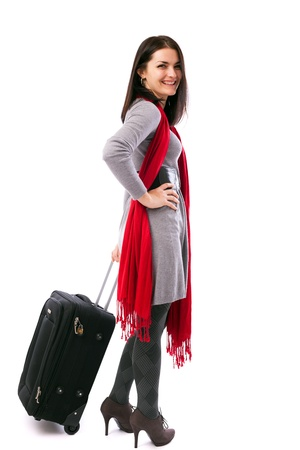 Full length portrait of a young traveler woman holding a luggage isolated on white background photo