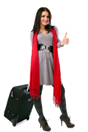 Full length portrait of a young traveler with luggage showing thumbs up isolated on white background photo
