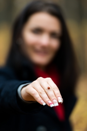 Maro of a ladybug walking on a young woman's hand. Selective focus on the insect Stock Photo - 16519520