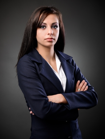 Studio portrait of a latin businesswoman in suit, against dark background photo