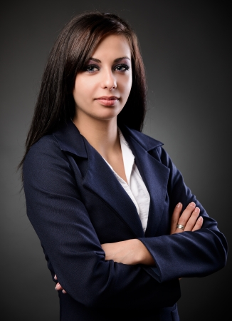 Studio portrait d'une femme d'affaires en costume latin, sur un fond sombre