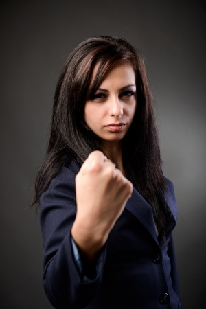 Young latin businesswoman showing her fist with a combative attitude photo