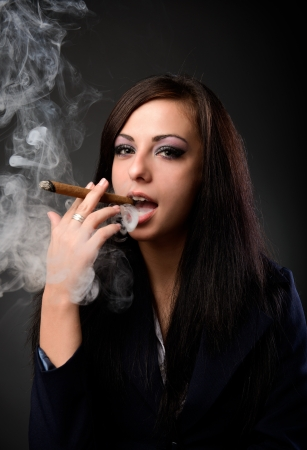 Closeup portrait of a young businesswoman smoking cigar and blowing smoke, on dark background photo