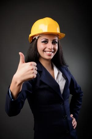 Youn femme ingénieur en construction avec casque faisant thumbs up signe Banque d'images