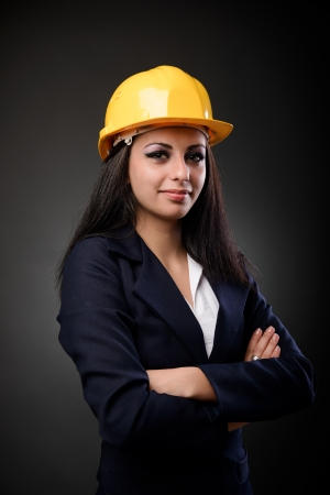 Young latino construction woman with hardhat and arms folded photo
