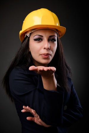 Young engineer lady with hardhat blowing kisses to the camera photo
