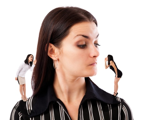 Businesswoman undecided which of her elf businesswomen advice to follow  Stock Photo - 16663396