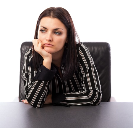 Closeup portrait of a young businesswoman thinking while sitting at desk photo