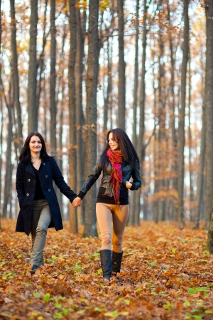 Full length portrait of two happy girlfriends walking in the woods while holding hands photo