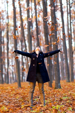 Full length portrait of a young woman playing with dried leaves in the woods photo