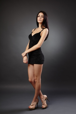 Seductive young hispanic woman in black dress, studio full length portrait photo