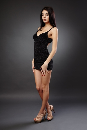 Seductive young hispanic woman in black dress, studio full length portrait Stock Photo - 16891139