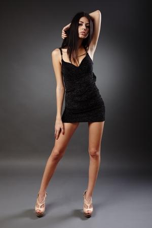 Seductive young hispanic woman in black dress, studio full length portrait Stock Photo - 16891160