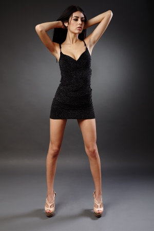 Seductive young hispanic woman in black dress, studio full length portrait Stock Photo - 16891159