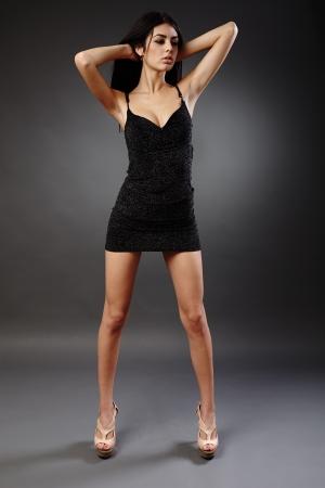 Seductive young hispanic woman in black dress, studio full length portrait Stock Photo - 16891159