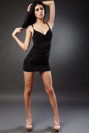 Seductive young hispanic woman in black dress, studio full length portrait Stock Photo - 16891130