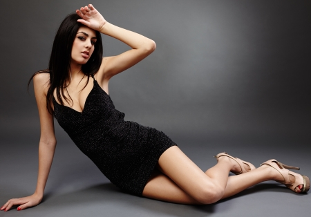 Glamorous hispanic young woman lying on the floor, studio portrait photo