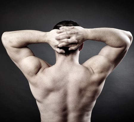 Back of a muscular man naked with his hands behind his head, studio shot photo