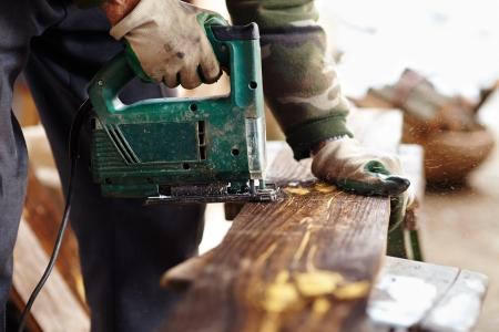 Homme avec des gants de protection à l'aide d'une scie électrique pour couper une planche Banque d'images