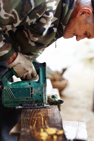 Old man with protection gloves using an electric saw to cut a plank photo