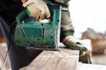 Man with protection gloves using an electric saw to cut a plank Stock Photo - 17324684