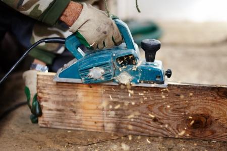 Mann mit Schutzhandschuhen mit einem elektrischen Schaber plane eine Planke