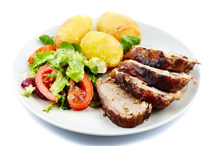 Closeup of a baked tenderloin with garnish of potatoes, lettuce and tomatoes on a plate photo